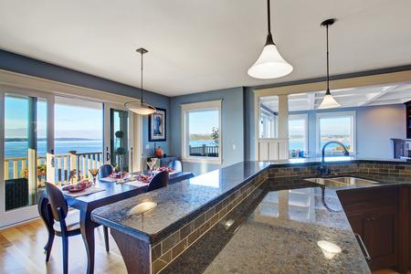 진한 갈색 캐비닛과 화강암 상단이있는 고급 주방. 주방에는 식사 공간과 도보 데크가있는 슬라이딩 도어가 있습니다.