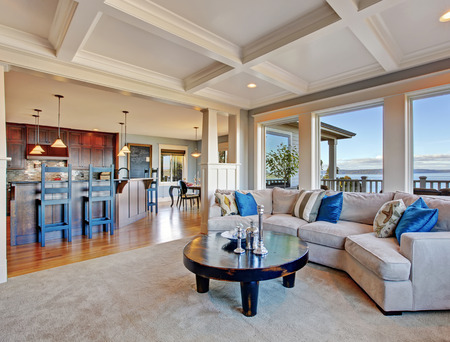open floor plan: Luxury house with open floor plan. Cozy living room in light tones with comfortable sofa and coffee table