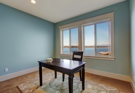 Simple office room in light blue color and bay view. Dark brown desk with chair