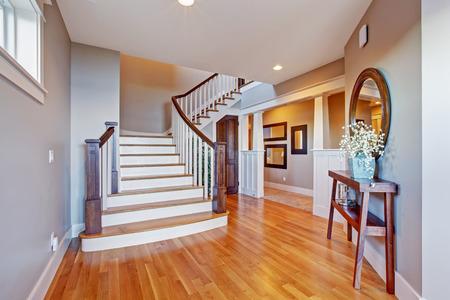 white trim: Bright hallway with wooden staircase. Staircase with white railings and brown trim