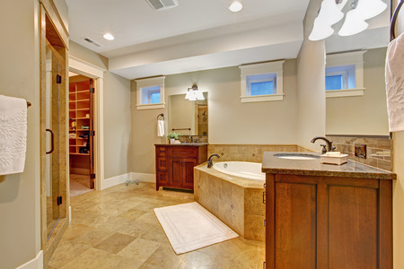 walk in closet: Luxury bathroom with granite tile trim. Spacious bathroom wtih corner bath tub, two vanity cabinets and walk in closet