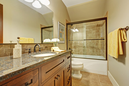 Bathroom interior with screened bath tub, wooden vanity cabinet with drawers and granite top