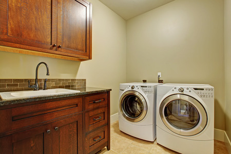laundry room: Laundry room with modern appliances, dark brown vanity cabinet with drawers. Stock Photo