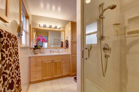 bathroom design: Bathroom interior with maple bathroom vanity cabinet and glass door shower