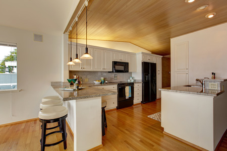 kitchen cabinets: Kitchen room with paneled ceiling, white cabinets with black appliances. Granite counter top with bar stools