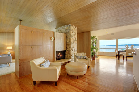 wood ceiling: Luxury house interior. Sitting area with leather amrchairs and leather ottoman. Cabinet with fireplace and rock wall trim Stock Photo