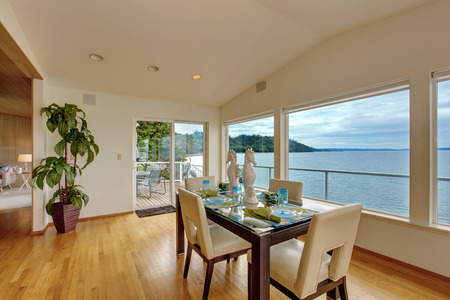 bay area: Luxury house interior. Bright elegant dining area with glass wall and  scenic bay view. Room has exit to walkout deck Stock Photo
