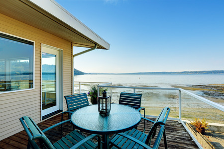 Luxury house with screened walkout deck with patio area overlooking private beach and  Puget Sound view in Burien, WA. Stock Photo
