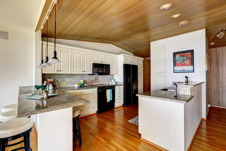 black appliances: Kitchen room with paneled ceiling, white cabinets with black appliances. Granite counter top with bar stools