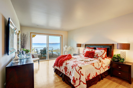 Romantic master bedroom interior with walkout deck. Bed with white and red bedding, decorated with pillows