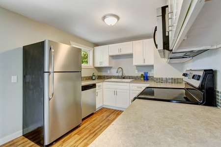 kitchen cabinets: Furnished kitchen room with white cabinets and steel appliances. Kitchen with hardwood floor