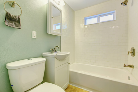 white trim: Mint bathroom interior with white tile wall trim, white bath tub, washbasin cabinet and toilet Stock Photo