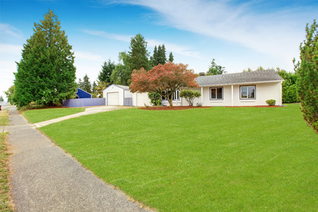 front of: Simple house exterior in white color. Large front yard with lawn and trees Stock Photo