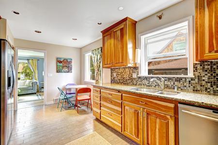 back kitchen: Kitchen maple storage combination with steel kitchen appliances and mosaic back splash trim