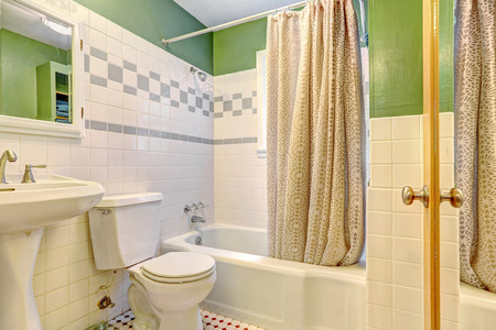 white trim: Bathroom inteiror with green wall and white tile trim. Bath tub with beige curtain Stock Photo