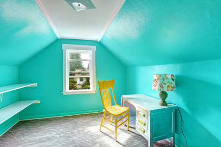Small bright turquoise room with vaulted ceiling and shelves attached to the wall. Room has desk and chair photo