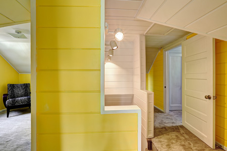 upstairs: Upstairs hallway with bright yellow wall and plank trim Stock Photo