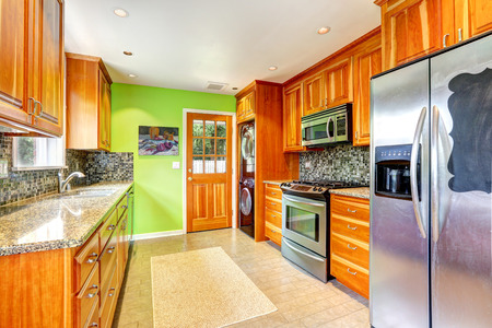 granite kitchen: Maple kitchen cabinets with mosaic back splash trim and granite tops. Bright kitchen room with green wall