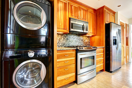 home appliances: Kitchen maple storage combination with steel kitchen appliances and black laundry appliances