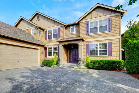 luxury home exterior: Luxury house. Clapboard siding exterior with purple elements. Entrance porch with trimmed hedgeds along the walls and garage with driveway