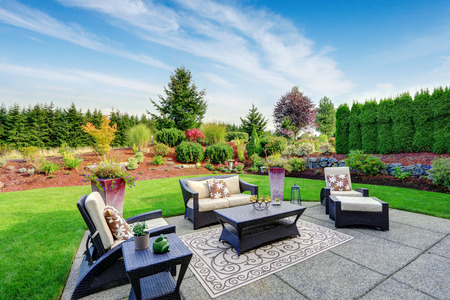 Impressive backyard landscape design. Cozy patio area with settees and table Banco de Imagens