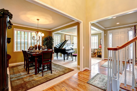 open floor plan: Luxury house interior with open floor plan. Dining area and living room with grand piano