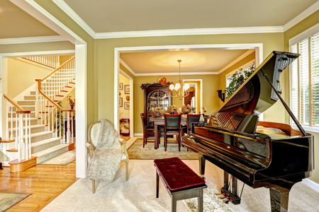 and the area: Cozy family room interior in luxury house. Room with grand piano. Dining area and white staircase Stock Photo