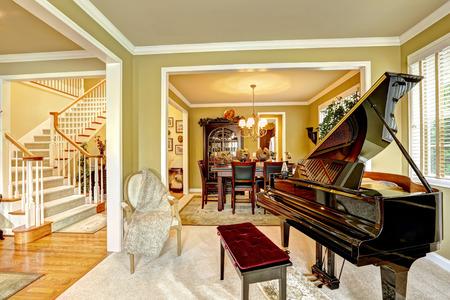 Gemütliches Familienzimmer Interieur in Luxus-Haus. Zimmer mit Flügel. Essbereich und weiße Treppe
