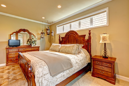 Luxury bedroom with carved wood bed, nightstand, vanity cabinet with mirror and decorative lanterns photo