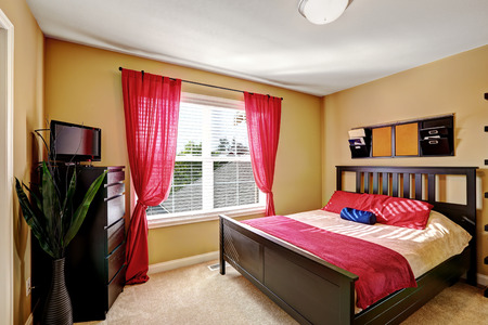 brightness: Simple yet practical bedroom design with dark brown bed, dresser and red decorative elements to enhance brightness of the room Stock Photo
