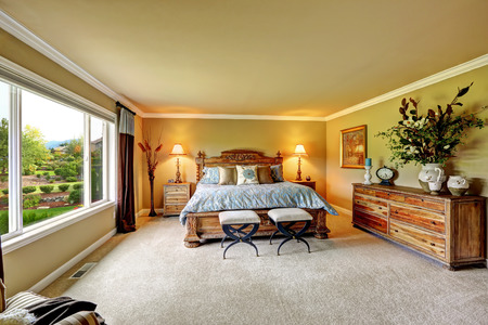 Spacious luxury bedroom with carved wood bed, nightstands and dresser decorated with flowers photo