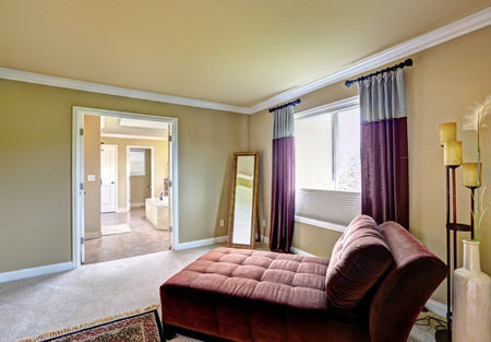 Sitting area with comfortable settee and mirror in the corner. Master bedroom interior Stock Photo