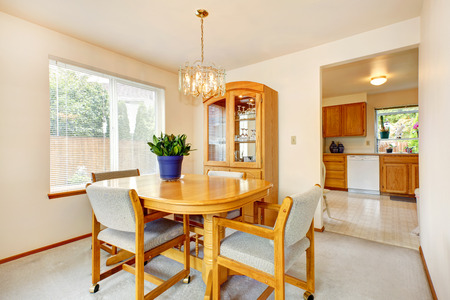 Bright dining area with maple dining table set and storage cabinet with glass door photo