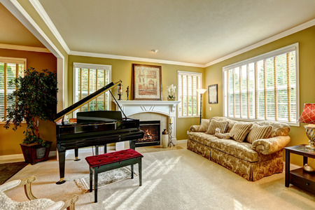Cozy family room interior in luxury house. Room with grand piano, fireplace and brown sofa