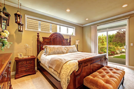 nightstand: Luxury bedroom with carved wood bed, nightstand, ottoman and decorative lanterns. Room has exit to backyar area