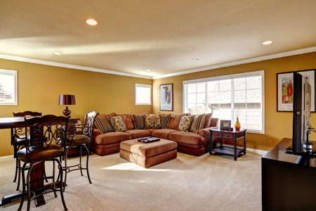 Cozy family room interior in luxury house. Room with comfortable couch and wooden table with stools