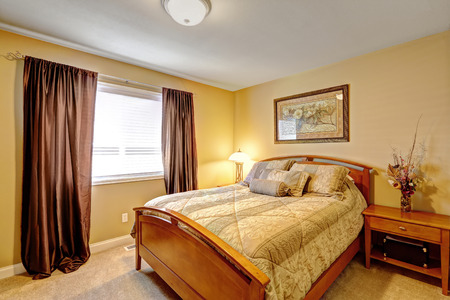 nightstand: Warm bedroom interior in light tones with wooden bed and nightstand