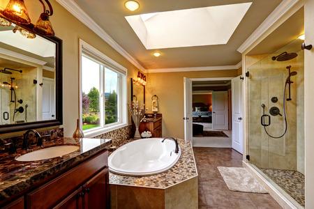 天窓付けの豪華なバスルームのインテリア。モザイク トリムと 2 つの木製の虚栄心のキャビネット付きバスタブ