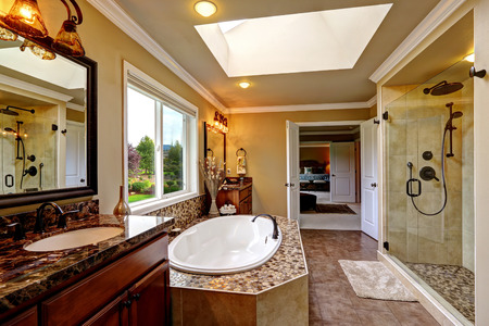 trims: Luxury bathroom interior with skylight. Bath tub with mosaic trim and two wooden vanity cabinets Stock Photo