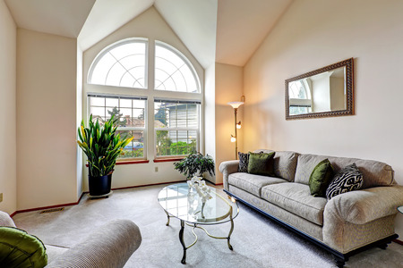 Luxury family room in soft creamy tones with hight ceiling and arch window. Room with sofa and armchair, glass top coffee table. Room decorated with green plants