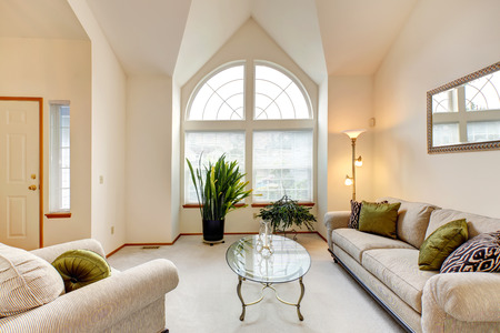 Luxury family room in soft creamy tones with hight ceiling and arch window. Room with sofa and armchair, glass top coffee table. Room decorated with green plants photo