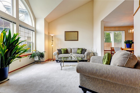 Luxury family room in soft creamy tones with hight ceiling and arch window. Room with love seat and armchair, glass top coffee table, decorated with green plants photo