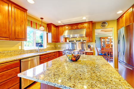 back kitchen: Shiny luxury kitchen room with island, granite tops, steel refrigerator, dishwasher, stove and hoood