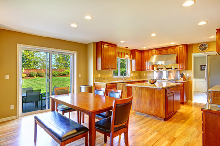 Luxury kitchen room with island, dining table set and exit to backyard patio area Stockfoto