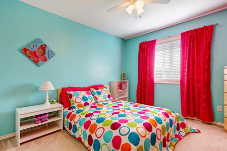 azul turqueza: Interior del dormitorio alegre de color turquesa con brillantes cortinas rojas y ropa de cama colorida Foto de archivo