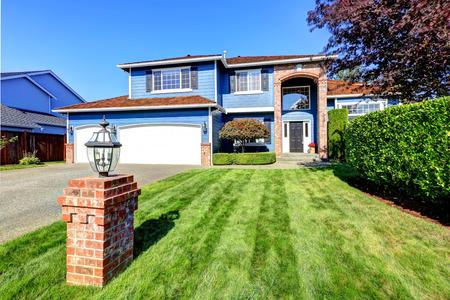 Lichtblauw huis buitenkant met bakstenen trim en pannendak. Garage met oprit en voortuin landschap met gazon en heggen Stockfoto