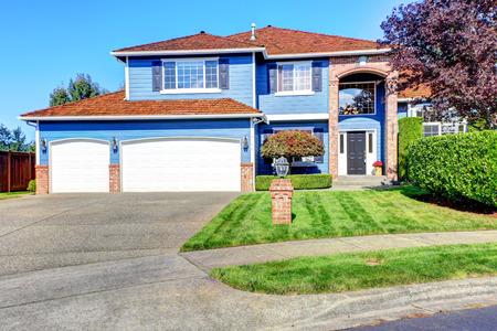 밝은 파란색 집 외관 벽돌 트림 및 타일 지붕. 차도 및 앞뜰과 잔디밭 및 트림 헤지스가있는 차고