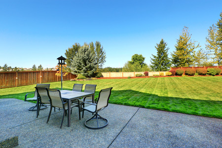 Patio area overlooking backyard landscape. Dining table with chairs and lantern