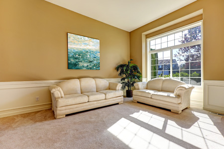 Bright sun room interior with large french window and light tones sofa and love seat photo