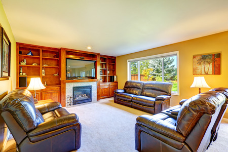 Family room with rich leather furniture set, cozy fireplace and tv. Room has built-in storage combination